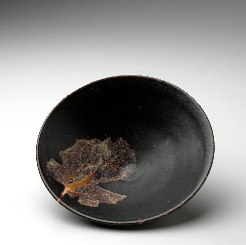 conical shaped tea bowl; dark brown glaze with single leaf design at interior; foot unglazed; has own storage box