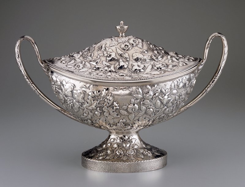 boat-shaped footed tureen with domed cover and two handles; decorated overall with raised foliage, flowers, fruit and birds