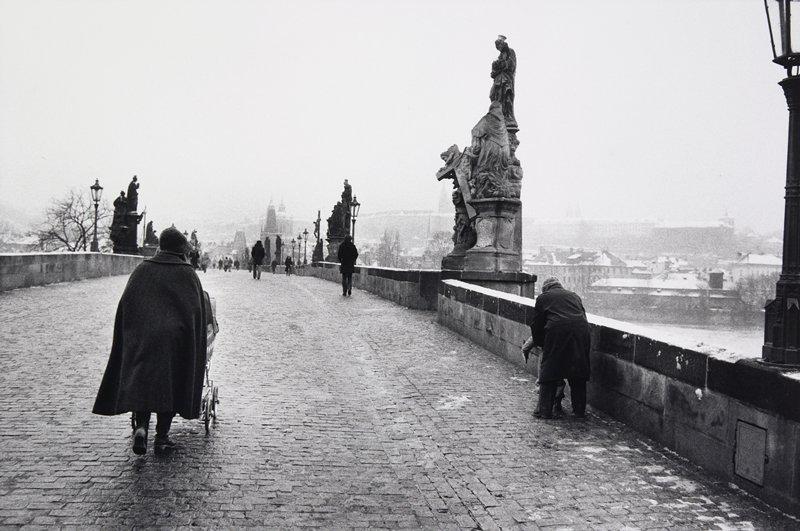black and white photo of brick paved bridge; woman pushing a pram on left