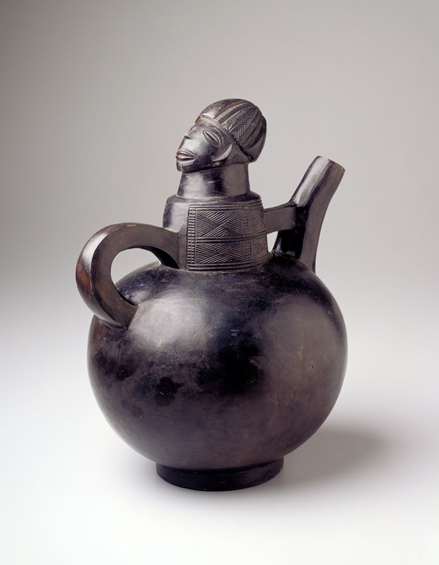 Round body with short foot; handle and thick spout; neck decorated with incised geometric designs; human head, facing handle, on top of neck with caplike hairstyle; black