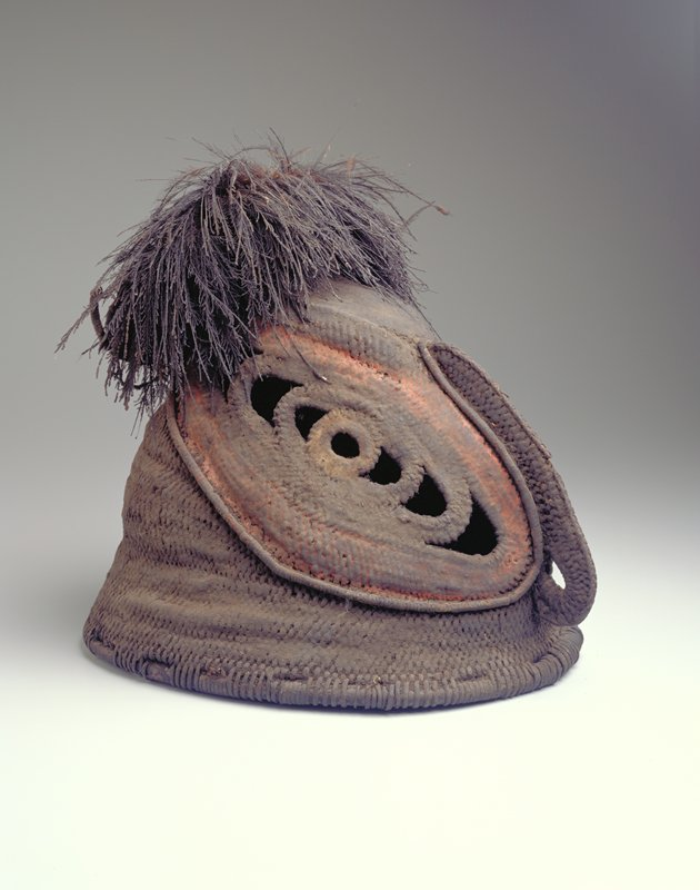 head-covering, helmet-type mask with very large eyes and beaklike nose; eyes are red, brown and yellow; small ears with feather earring in PL ear and feather topknot