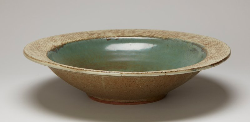 large bowl with slightly sloping lip; light and dark tan textured border; mottled green with brown interior; tan exterior
