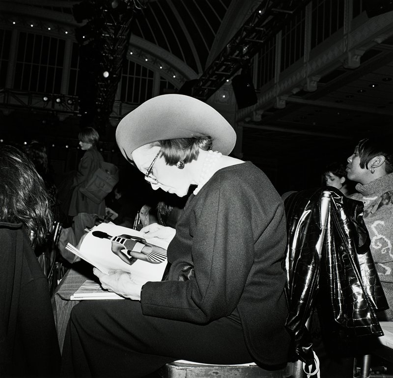 seated woman seen from PL, wearing a dark jacket and skirt, glasses, hat and large pearl necklace, reading a fashion magazine; other figures at R, L and in background