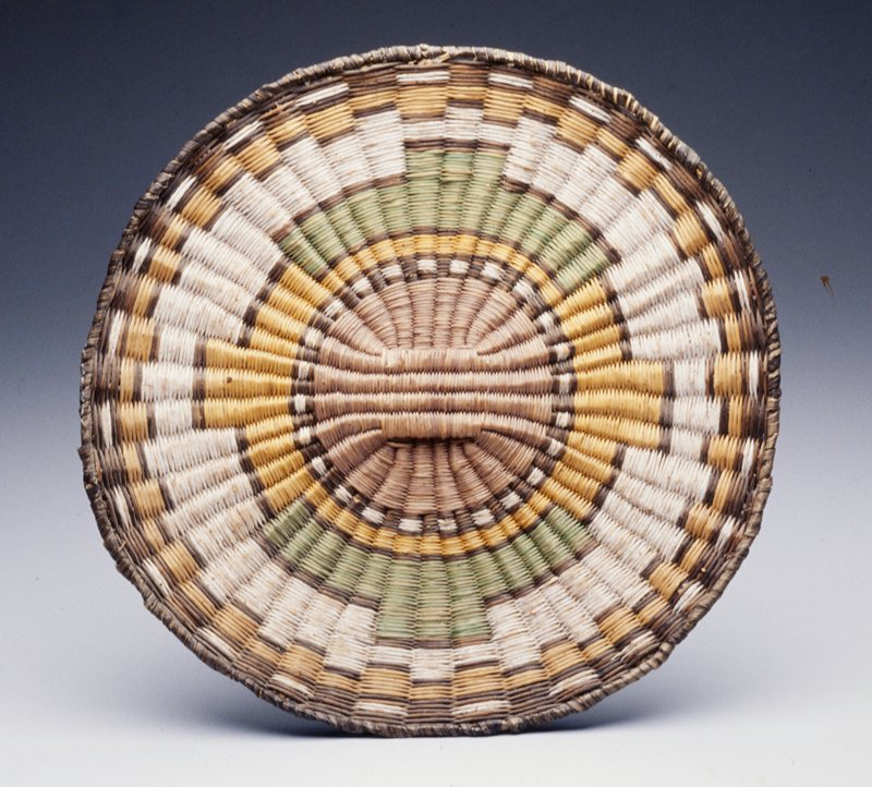 Nearly flat basket with raised element in center; geometric circle design at center in brown, yellow, white, green and blue dyed fibers