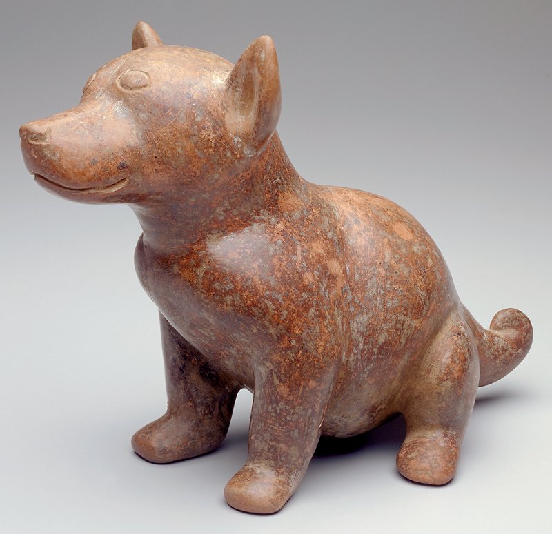 Small seated dog with short pointed ears and a short tail, curling over on top; uneven incised eyes