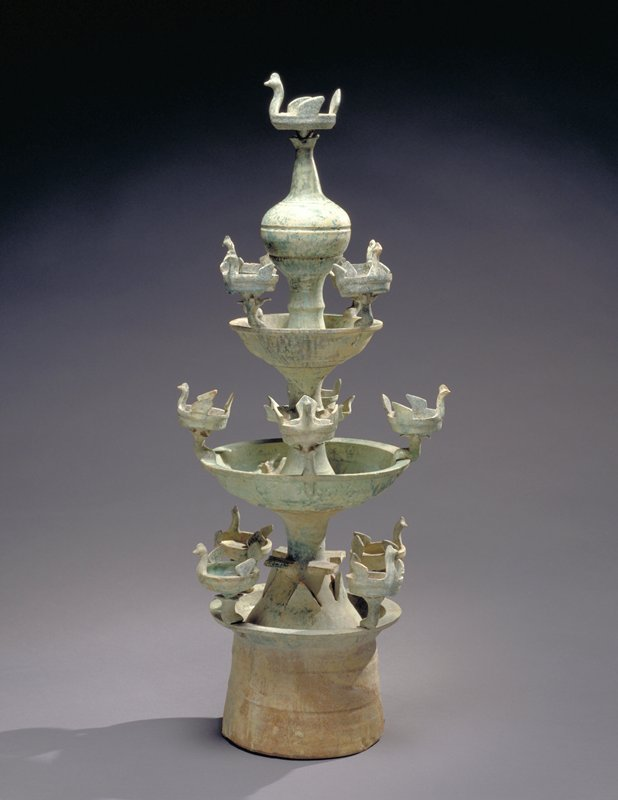 3 sections; green glaze; 3 tiers, each with 4 small basins with stylized bird's heads, wings and tail, with one larger basin at top; 2 dogs running near central element of middle section