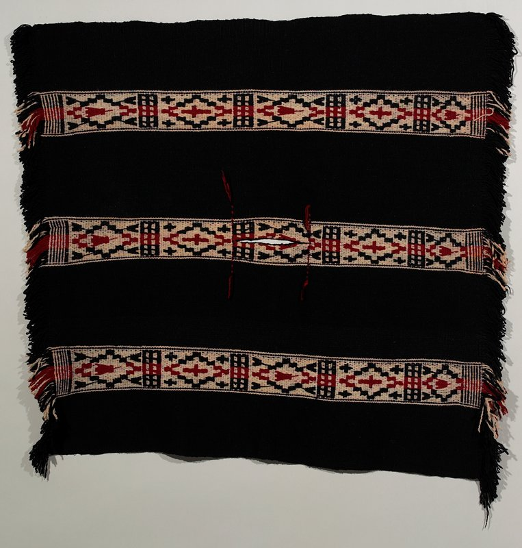"""3 white, red and black brocaded stripes on black background; 4"""" long fringe on both ends; vertical 10"""" long button hole in the central part for head"""