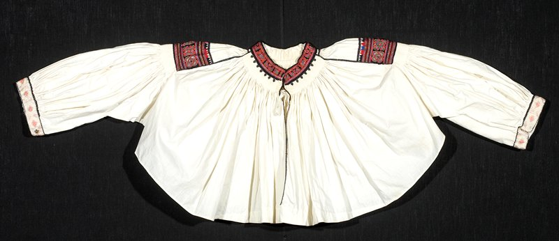 white smocked blouse with red, black, green, yellow, blue, gold embroidery; stylized floral designs at shoulder and neck; pink and cream embroidered ribbon at cuffs with black embroidery binding