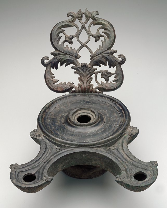 Bowl with short stem and lobed foot; two protruding elements at front with floral motif decorations; large openwork decorative element above handle with flower and leaf designs