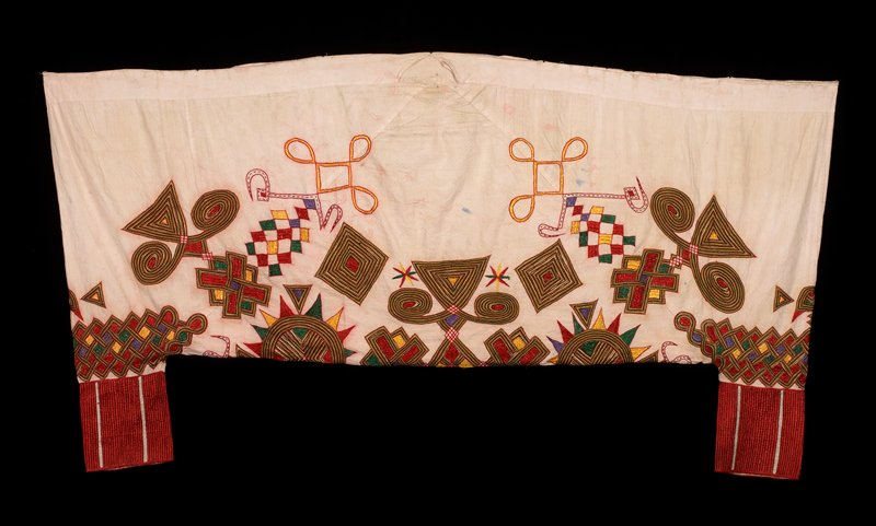 light pink fabric embroidered with geometric and curvalinear designs in purple, red, black, green and yellow
