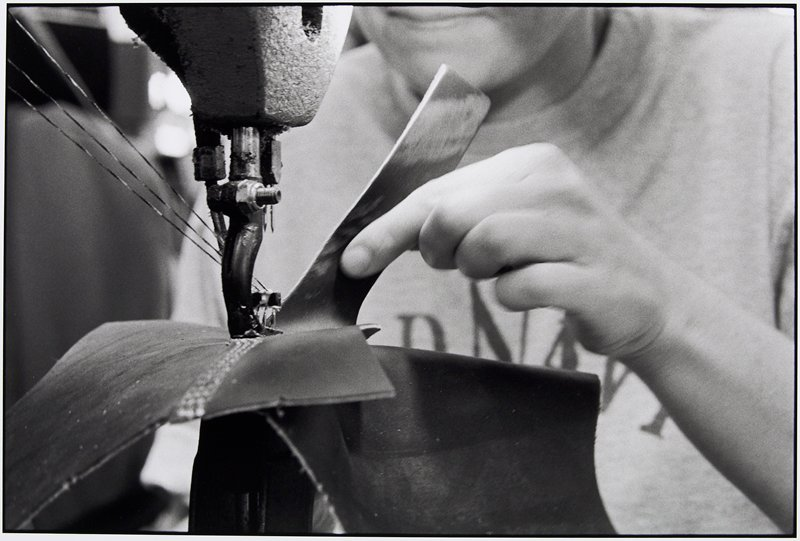 close-up of a hand guiding leather through a sewing machine