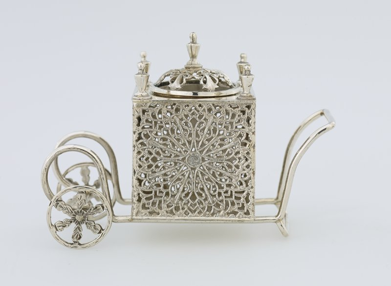 Spice box in the form of a square pushcart with floriform filigree designs on sides; domed openwork cover; movable wheels with floral spokes