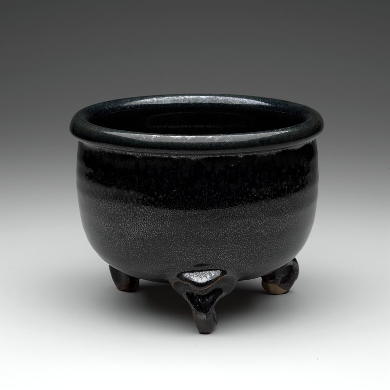 """oil spot"" black glaze; outward-rolled lip; rounded bottom; 3 molded feet"