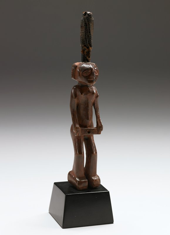 standing figure of a woman holding a rectangular wooden bar or box between her hands under her navel; 2 sticks tied together with knotted string and encrusted with a brown paste inserted into the top of the head; 2 holes, in the back and front bar, carry magical ingredients; surface is reddish with ngula; neck shows traces of a former bead necklace; geometrical coiffure and inclused toes; glossy patina