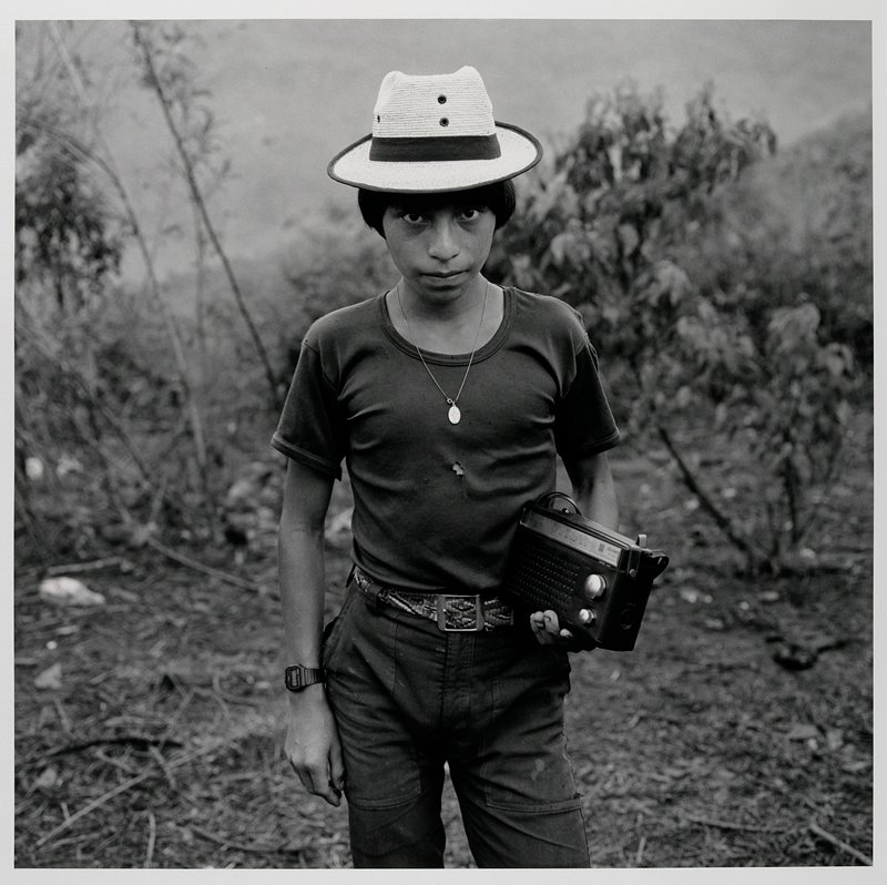 standing young man wearing a hat, torn t-shirt, pants with multicolored belt, watch and necklace, holding a radio in his PL hand