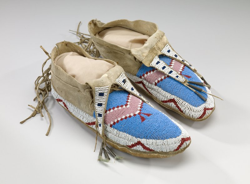 rawhide soles; tanned uppers; bifurcated tongues; white, red, pink and blue beads in geometric designs; tin cones and feathers at tongue ends