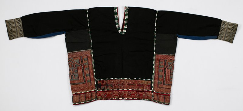 black with blue under long sleeves; V neck, front and back; blue and white woven cuffs; panels on sides and bottom with intricate geometric embroidery, predominately in red, rose and dark brown; trimmed with green, blue and white beads