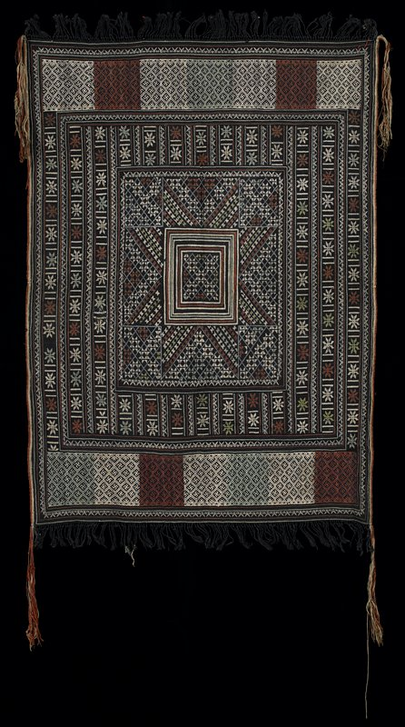 black panel with black knotted fringe on short sides and long brown and tan tassels at corners; squares, rectangles and bands of flower or star, swastika and other geometric motifs embroidered overall in white, pale green, brown and blue