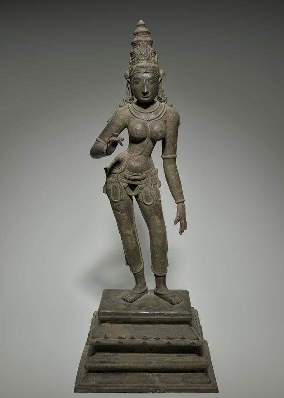 standing female figure with bare breasts, in contraposto pose; wearing tiered conical headdress with wheel on back, necklaces, bracelets, rings, heavy belt, gauzy form-fitting slacks, anklets; figure stands on a graduated base; PL arm down, PR hand upraised