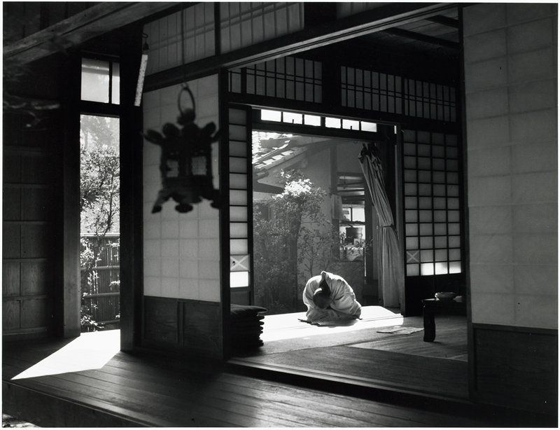 hunched figure seated on a sunny porch; view from interior; small garden behind porch
