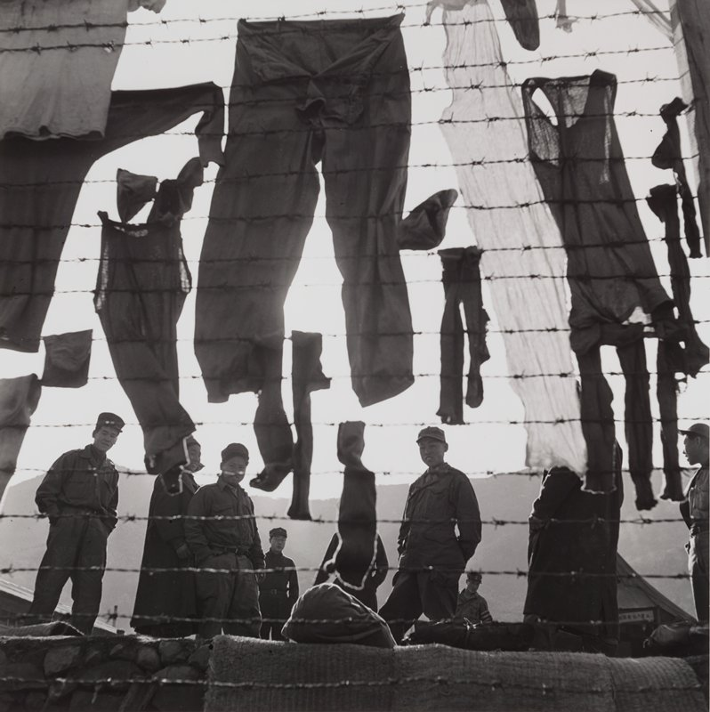 soldiers in background behind barbed wire; drying laundry hanging on barbed wire