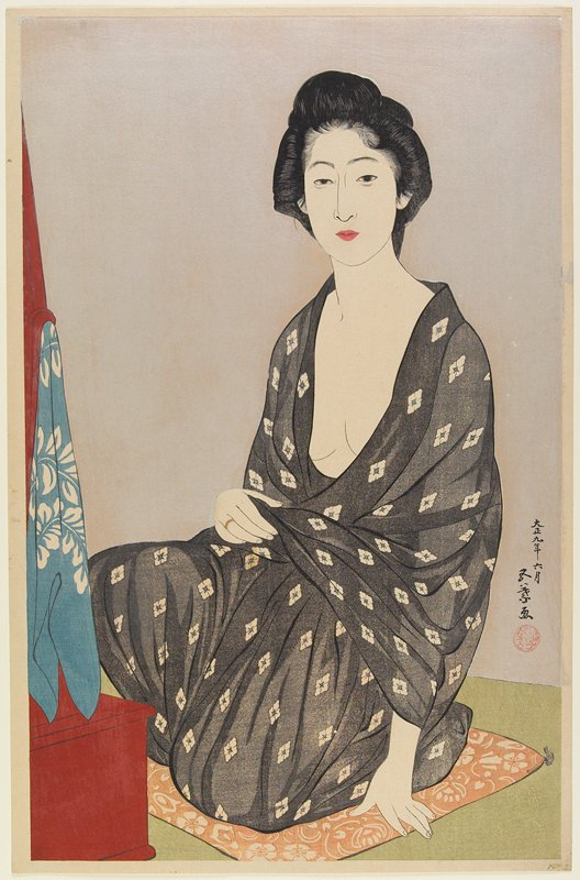 woman wearing an open black kimono with white flowers, seated on an orange cushion with white flowers; shiny silver ground