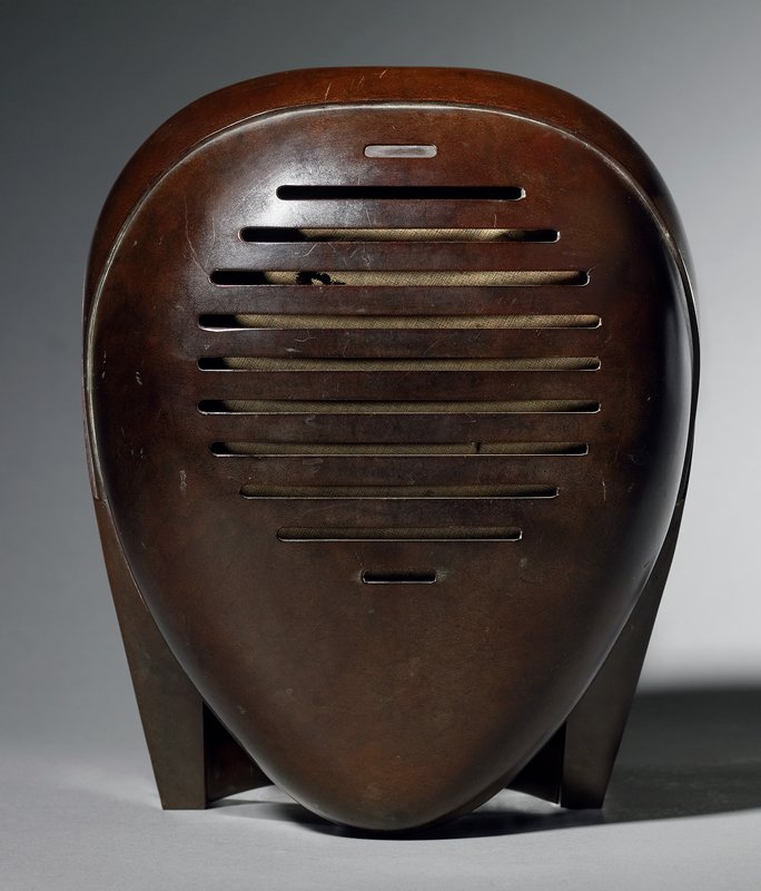 """ovoid shaped; horizontal indentations across front; horizontal """"handle"""" at bottom at back; dial at bottom on back; dark brown; attached to black metal mount"""