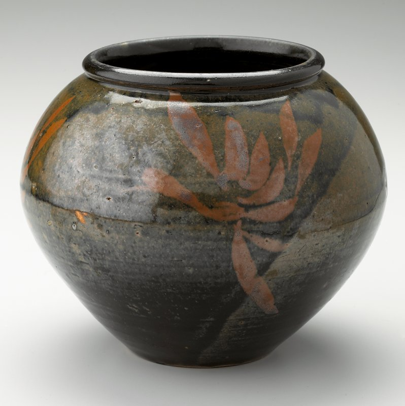 bulb-shaped jar with black glaze and rust-brown painted floral-like decoration