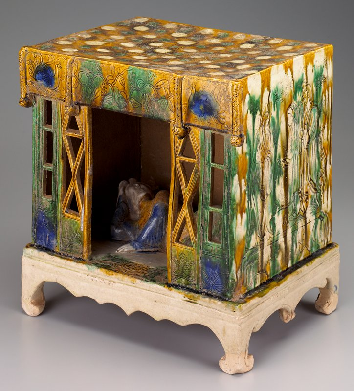 reclining figure inside a porch-form structure with open lattice screens at front; on small platform; sides and back incised with figures in a garden; cream, green and blue glazes
