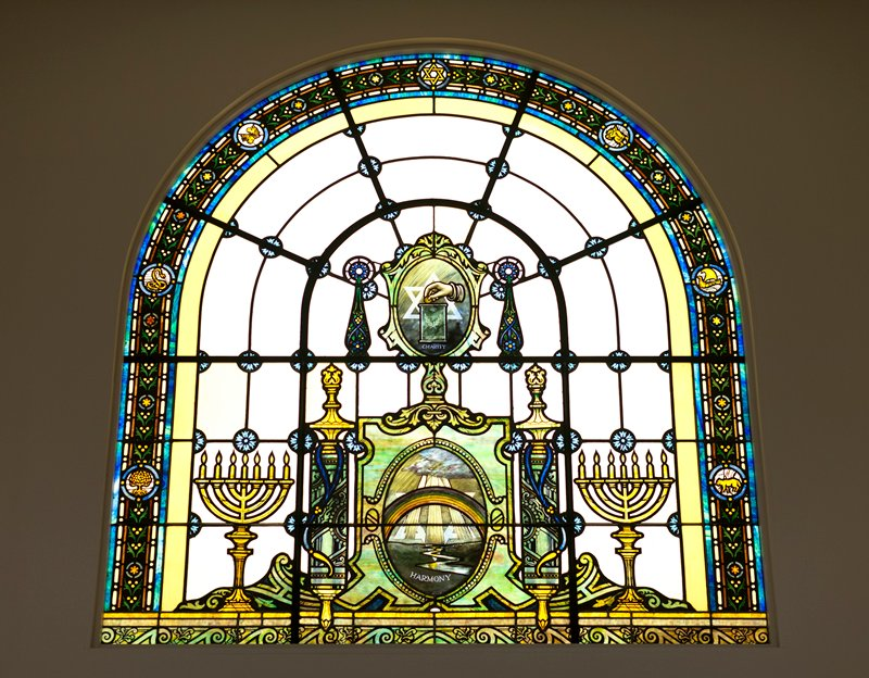 "oval glass cartouche, split horizontally at center into 2 parts; rainbow over 3 sunbeams extending downward from clouds, with large Star of David in background; ""HARMONY"", in blue, at bottom"