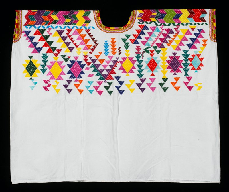 White, two-paneled cotton huipil with multicolored embroidery of abstract geometric patterns in turquoise, yellow, blue, orange, purple and pink.