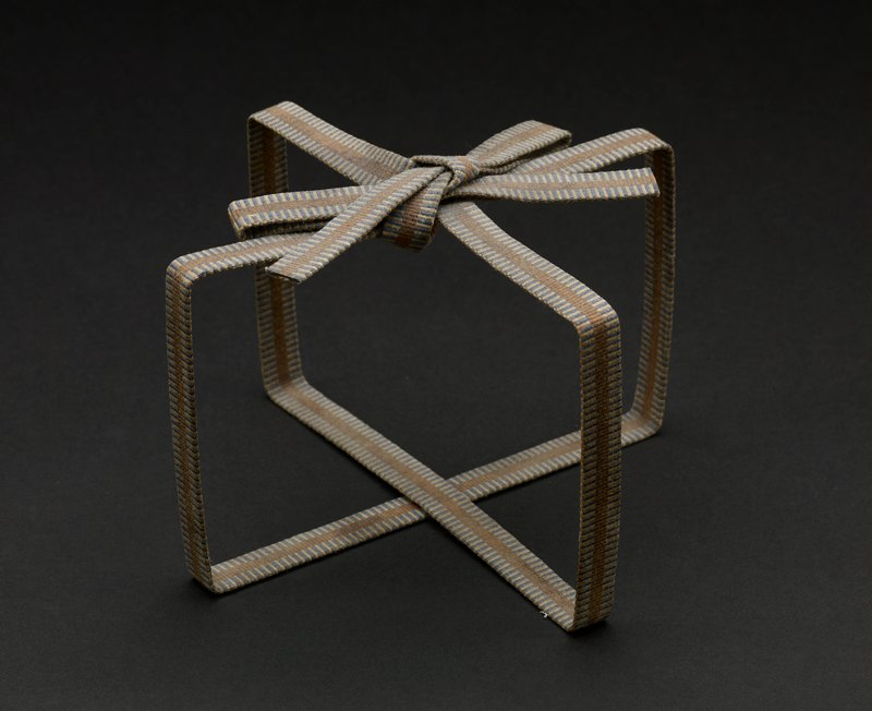 woven ribbon in blue, light tan and dark tan in striped pattern, formed and stiffened to mimic ribbon wrapped and tied in a bow around a box