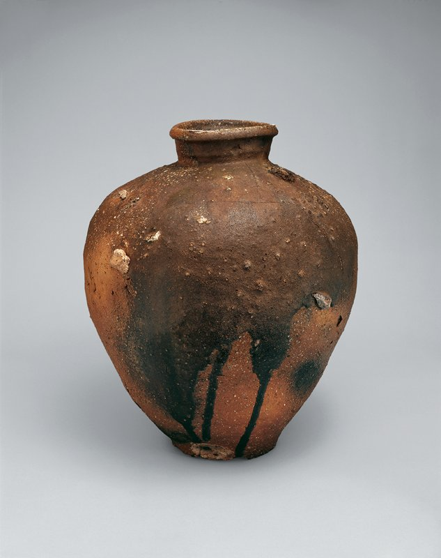 large jar with dark brown dripping over glaze and large rocky inclusions; wide shoulder, short neck, rolled lip; gnarled texture