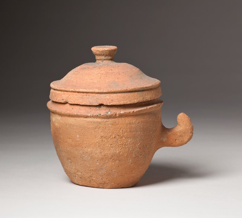 small earthenware cup with lid; cup has upward hooking handle on side and slightly protruding collar for lid; lid has small knob at top