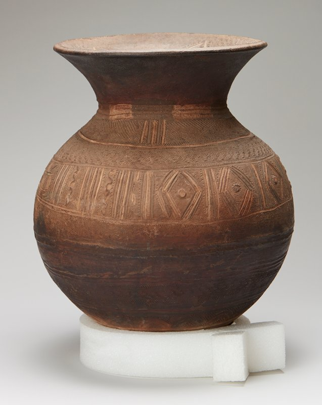rounded body flaring in at shoulder and flaring outward at mouth with wide lip; body and inner rim covered with incised geometric designs and patterns; traces of red and white pigments
