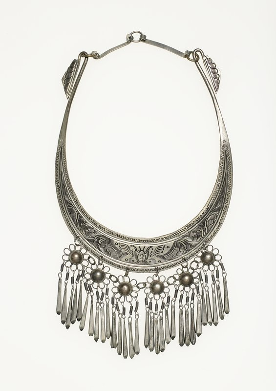 flat, wide silver collar with six floral drops, each with five tapered silver hanging pendants; collar has engraved design of moth at center and feathery scrolls