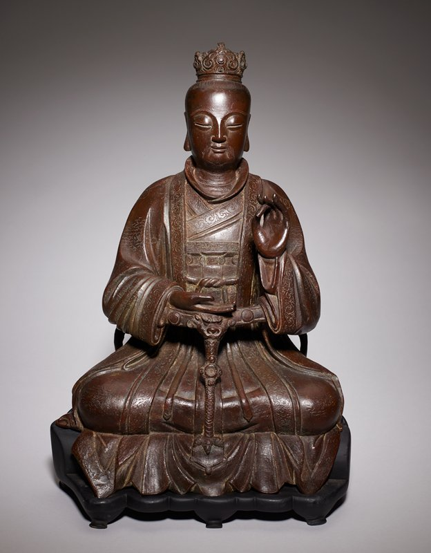 figure seated with legs crossed, one hand raised and one hand resting on a rail; dressed in flowing robes, crown on head; incised line details overall; rail curving around figure at front, supported behind at sides and in center front of figure; sculpture sits on a fitted black wood base