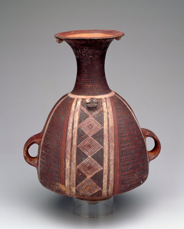 Jar, aryballos type, with two handles near base. A diminutive animal head in relief appears at the base of the neck. The front of the body is decorated with vertical panels separated by narrow bands, painted with lozenge and sawtooth motifs in red, black, mauve and white. The flaring neck is painted with horizontal bands of elongated lozenges in red and black, and under the rim is a border of reciprocal sawtooth pattern in the same colors. The back of the jar is painted brick red with a band of interlocking 'X' forms extending half-way around the shoulders. Aryballos (MWS)