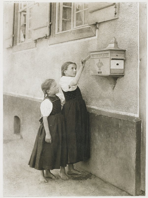 two barefoot little girls wearing matching dresses; taller girl is inserting a letter into a mailbox