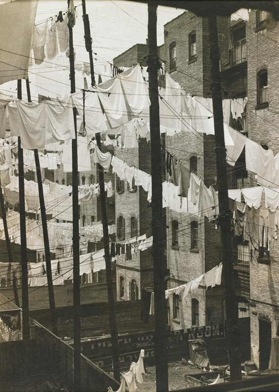 view of clotheslines hung with laundry, between brick apartment buildings and poles