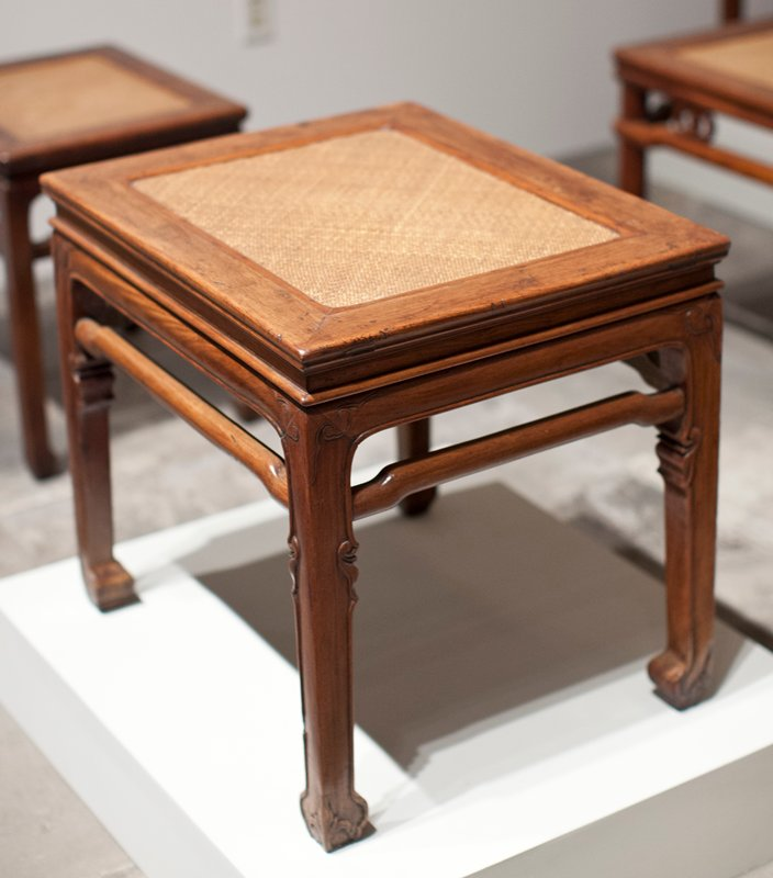 huanghuali rectangular stool, the typical mitred, mortice and tenon frame top with a soft matting seat with two curved transverse stretchers; outside edge of the frame of unusual profile with a concave center section curving down to a square shoulder below; recessed waist made separately from apron, with a raised prominent bead below; apron is mitred and half-lapped into the legs, carved with ruyi head lappets to the shoulder and a raised bead which follows the inside edge of the leg terminating in the horse-hoof foot; part of the way down the leg is a small hip carved with a leaf motif in conjunction with the raised bead; legs are joined by high hump-back stretchers, slightly recessed and convex to the outer face, and tenoned into the legs; outside edge of the horse-hoof foot is carved with a stylized leaf motif