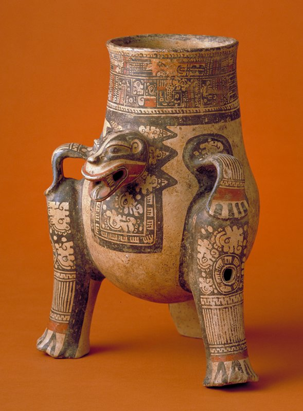 Tripod effigy vessel, large, with the head of a jaguar in high relief. Two legs, finished at the base of the neck with rigid ring handles formed of the jaguar's front legs, represent the hind legs and are pierced and contain pellets. The third support, in the form of a flattened tail, emerges from the back of the vessel. The jaguar head, an oblong, bib-like area below, the legs, and a wide band at the throat, are painted in polychrome with geometric designs on an orange ground. High polish.