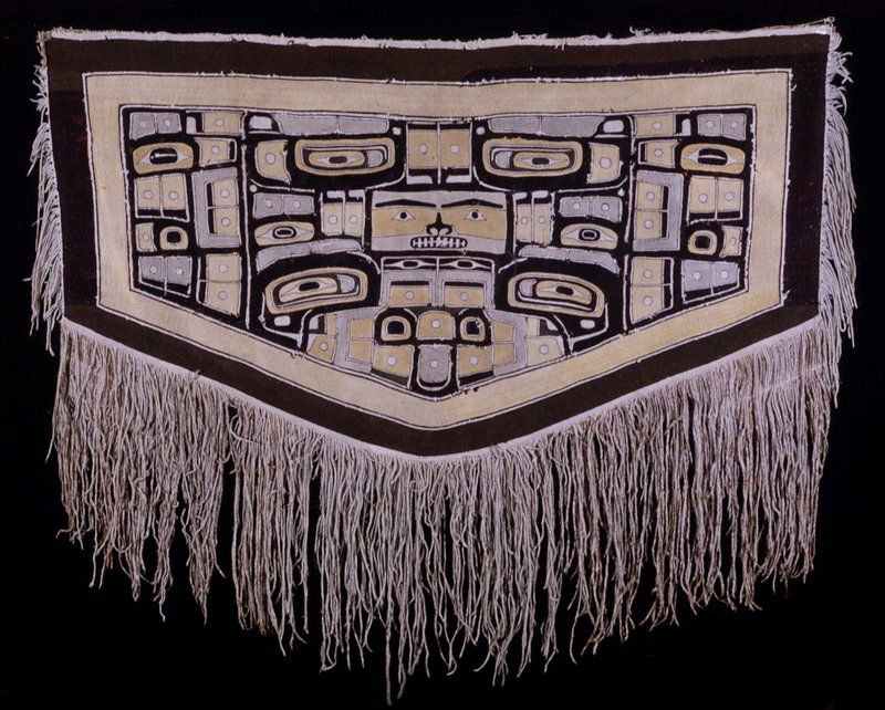 Chilkat blankets are woven by the women of the Chilkat branch of the Tlingit tribe, using patterns devised by Chilkat men. Warp is goat hair and yellow cedar bark twine. Dyes are dervived from hemlock bark, lichen and copper. Style and technique may be traced to the Tsimshian tribe. Fringe 20 inches on bottom, 8 inches on side. Catalog card: Gift of Mrs. Folwell W. Coan from the estate of Mrs. Eugene Carpenter. Mended 1974.