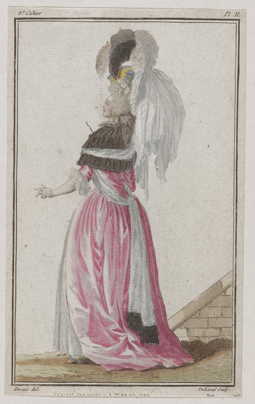Woman seen from behind in a white gown with pink overgown and a brown cape and large mostly white hat