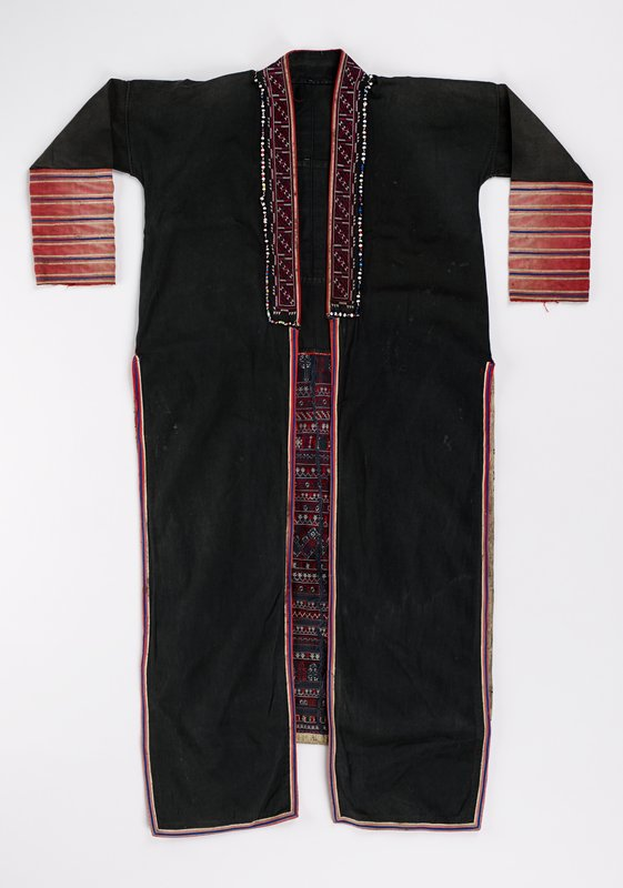 black body; slits at sides; sleeves and front hem decorated with red, white and blue linear applique; multicolored beads and purple and white embroidery around collar; geometric embroidery at center back and back lower panel with linear applique