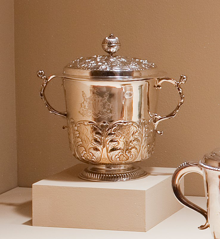 cup and cover, two-handled; slightly rounded at bottom, on a raised base with gadrooned band; the lower body is decorated with a deep band of repoussé acanthus leaves; the slightly domed cover, with a broad design of leaves in relief, is topped by a fluted ball finial; caryatid handles