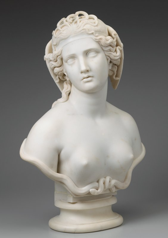 bust of a woman with a cluster of small snakes at the front of her head, wings at the side of her head; intertwined snakes below her breasts