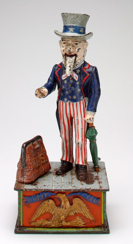 Uncle Sam wearing blue jacket with red pin striped pants and tall hat, holding green umbrella in left hand and standing on green and orange rectangular box; brown bag below his right hand on box