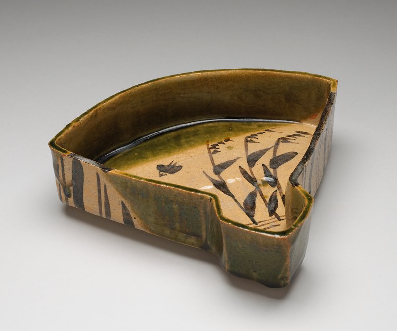 dish with vertical sides, in the shape of a fan; brown, green and tan glazes; grasses and two birds at interior; lines on exterior; three small loop feet; has storage box