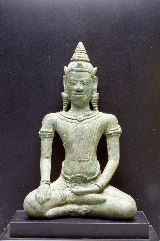 seated Buddha with PL hand palm up in lap and PR hand on knee; broad shoulders and very thin arms; wearing long earrings and pointed cap
